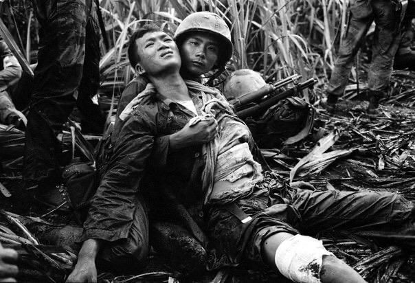 Южновьетнамский морпех успокаивает своего товарища, который был тяжело ранен северовьетнамскими партизанами в процессе их поиска на полях сахарного тростника в 12 км от Сайгона