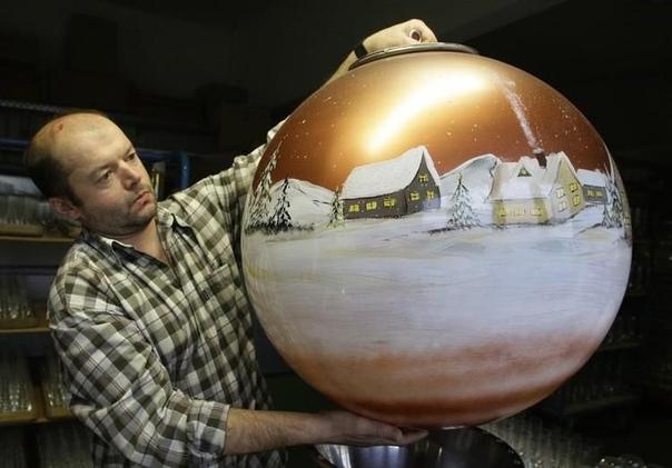Самая большая елочная игрушка Франц Патерноста держит стеклянное украшение для рождественской елки, сделанное на баварском стеклодувном производстве Josa, 17 декабря 2008 года. Компания