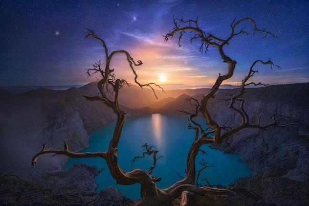 Снимок луны, сияющей над комплексом вулканов Иджен на острове Ява в Индонезии.